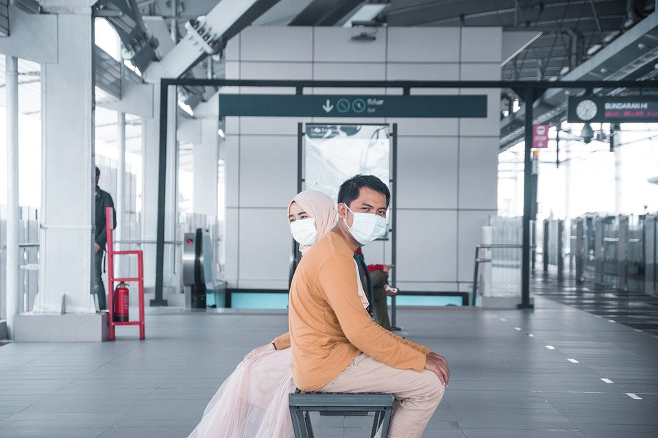 Two people sitting with masks on
