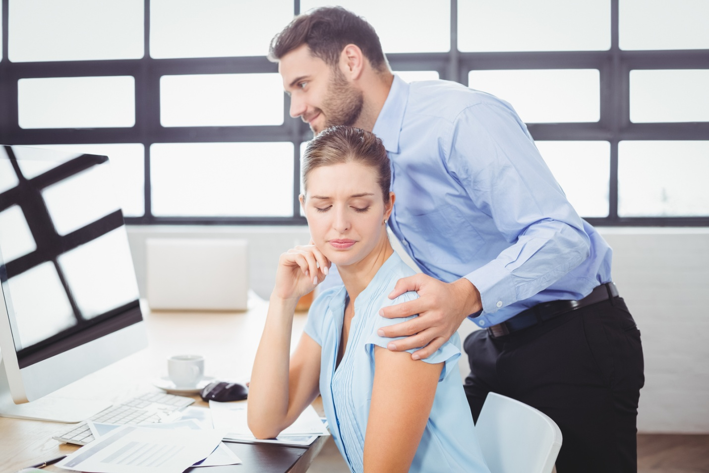 A male supervisor harasses a female employee by touching her inappropriately.